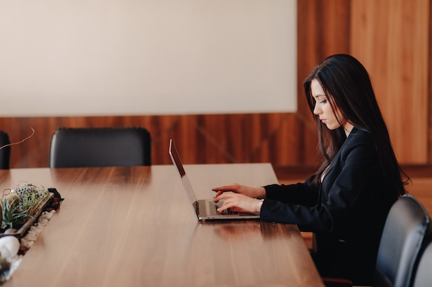 Muchacha emocional atractiva joven en la ropa del negocio-estilo que se sienta en un escritorio en una computadora portátil y un teléfono
