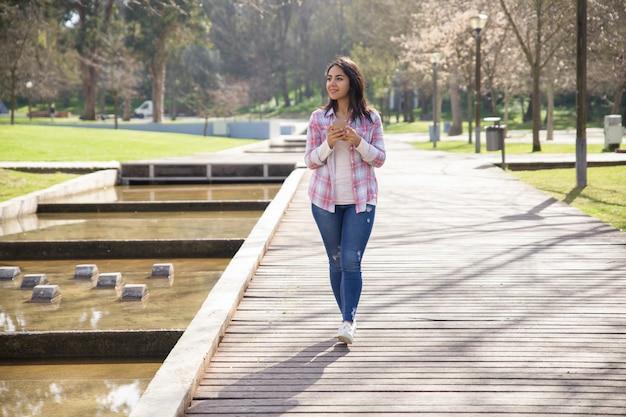 Muchacha encantada sonriente que disfruta de paisaje en parque de la ciudad