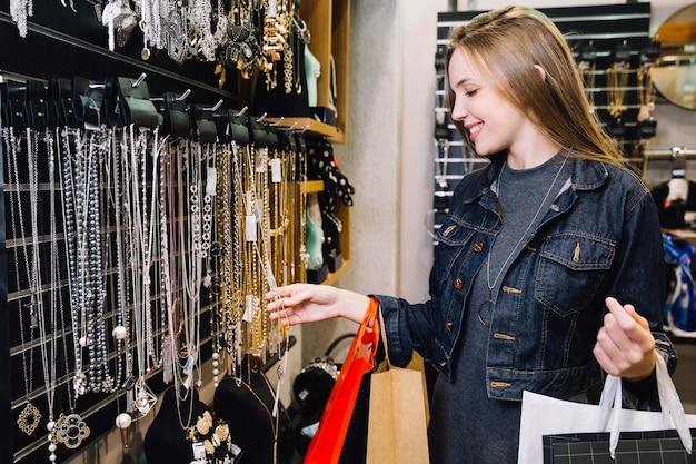 Muchacha encantadora que explora los accesorios en tienda