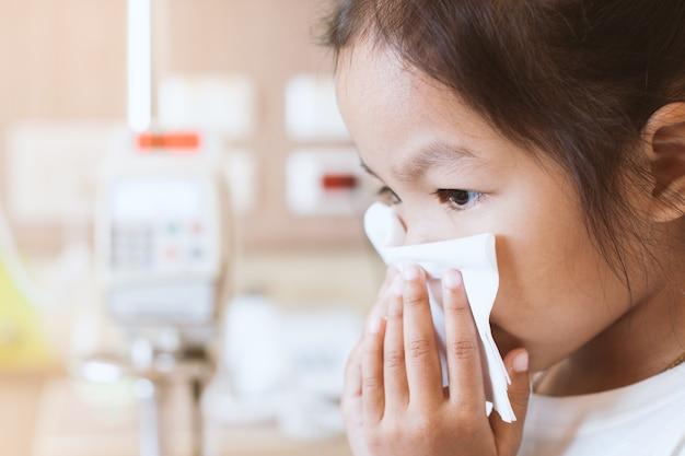 Muchacha enferma asiática del niño pequeño que limpia y que limpia la nariz con el tejido fino