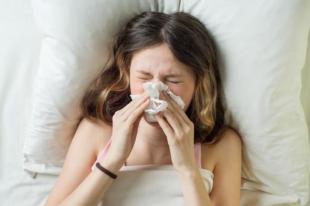 Muchacha enferma en cama que estornuda en pañuelo en dormitorio