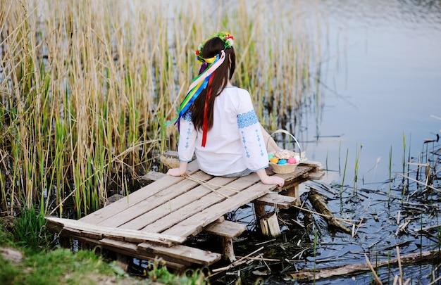 Muchacha eslava en la camisa ucraniana que se sienta en el puente con pascua