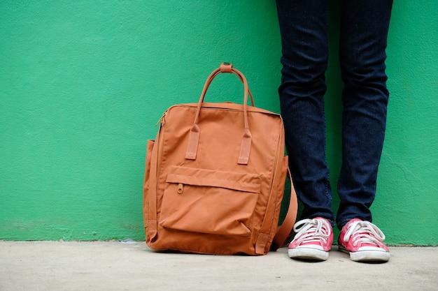 Muchacha del estudiante y bolso de escuela que se coloca sobre fondo verde de la pared con el espacio de la copia
