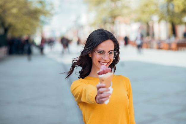 Muchacha del estudiante con el cono de helado al aire libre.
