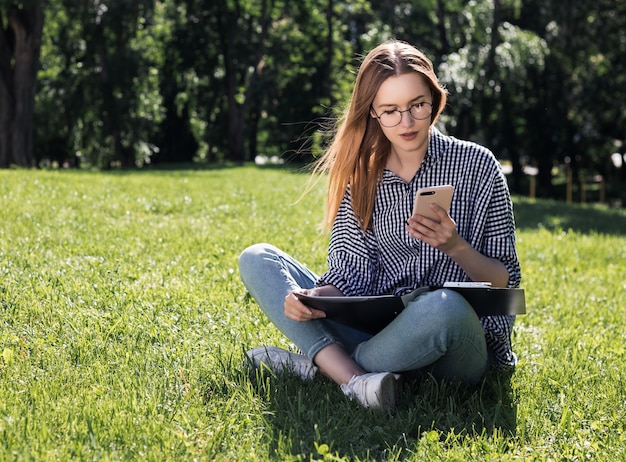 La muchacha del estudiante mira en su teléfono inteligente con una carpeta en sus manos que se sienta en la hierba en el parque