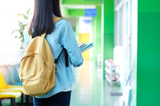 Muchacha del estudiante que sostiene los libros y el bolso de escuela que se colocan en el fondo de la escuela, educación