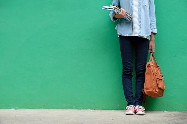 Muchacha del estudiante que sostiene los libros y el bolso de escuela que se colocan sobre fondo verde de la pared