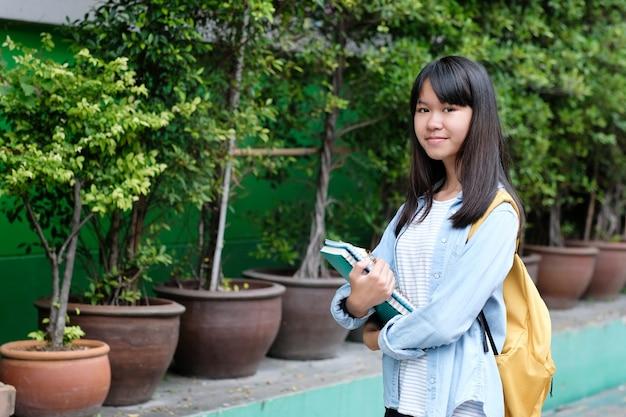 La muchacha del estudiante que sostiene los libros y lleva el bolso de escuela mientras que camina en fondo de la escuela