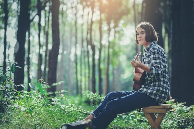 Muchacha de la felicidad que toca la guitarra del ukelele en el bosque grande.