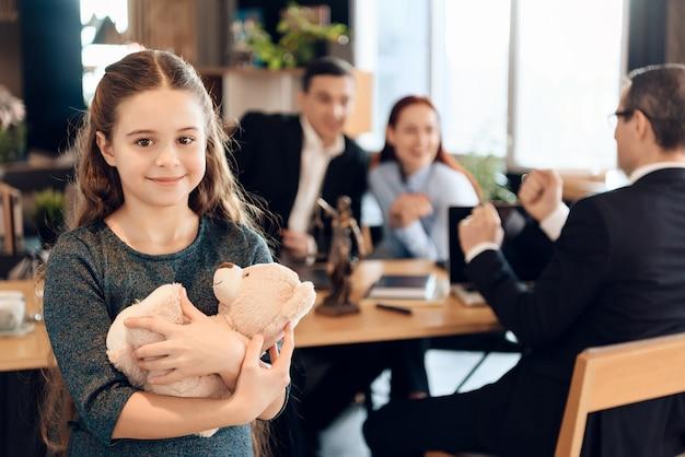 La muchacha feliz está abrazando el oso de peluche en la oficina del abogado de familia.