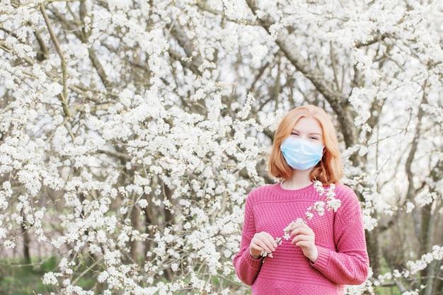 Muchacha feliz del adolescente en máscara médica en jardín floreciente de la primavera. concepto de distancia social y prevención del coronavirus.
