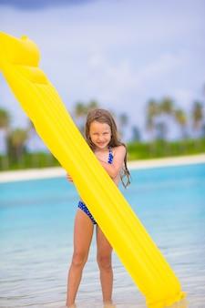 Muchacha feliz adorable con el colchón de aire inflable en la playa blanca
