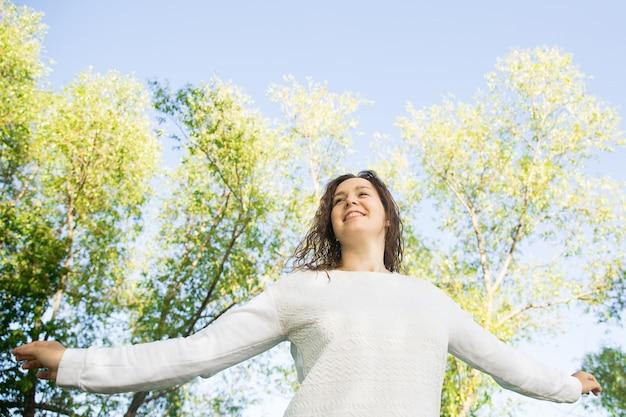 Muchacha feliz en blanco en el parque verde. caminando por la naturaleza