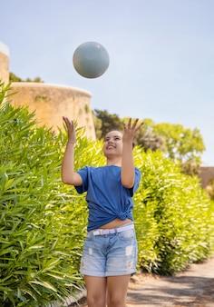 Muchacha feliz del escolar en camiseta azul que sostiene la bola al aire libre. niño lindo haciendo deporte, disfrutando jugando al fútbol y divirtiéndose en el parque. pasatiempos activos, concepto de estilo de vida saludable. maqueta de camiseta