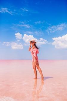 Muchacha feliz en un lago de sal rosado en un día de verano soleado. explorando la naturaleza, los viajes, las vacaciones familiares.