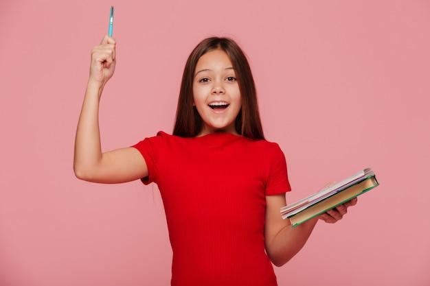 La muchacha feliz con el lápiz y los libros tiene e idea una sonrisa aislada