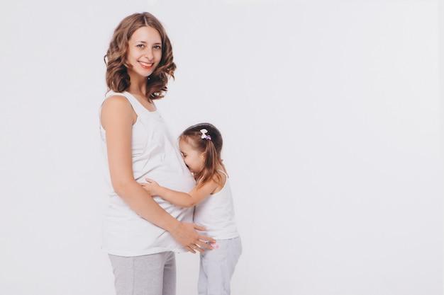 Muchacha feliz del niño que abraza el vientre de la madre embarazada, el embarazo y el nuevo concepto de la vida