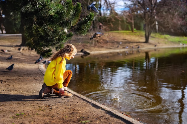 Muchacha feliz del niño en el suéter amarillo brillante que paga con agua al aire libre