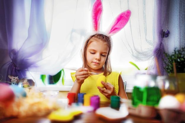 Muchacha feliz de pascua en orejas de conejo que pinta los huevos, niño pequeño en casa. vacaciones de primavera