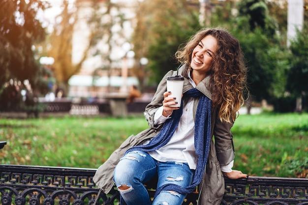 La muchacha feliz con el pelo rizado disfruta de la bebida al aire libre