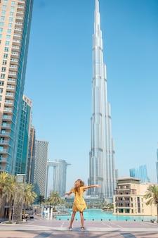 Muchacha feliz que camina en dubai con el rascacielos de burj khalifa en el fondo.