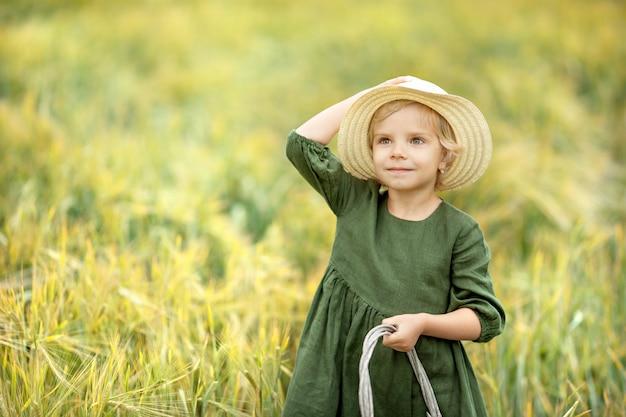 Muchacha feliz que camina en el trigo de oro, disfrutando de la vida en el campo. belleza de la naturaleza y campo de trigo. estilo de vida familiar al aire libre. concepto de libertad niña linda en el campo de verano