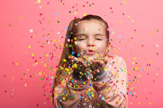 Muchacha feliz que celebra en un fondo rosado.