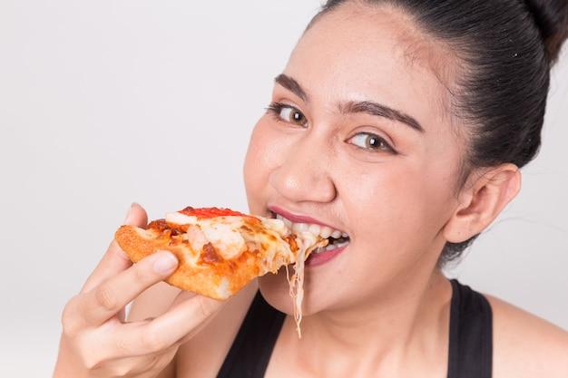 Muchacha feliz que come la pizza sabrosa. aislado en un fondo blanco.