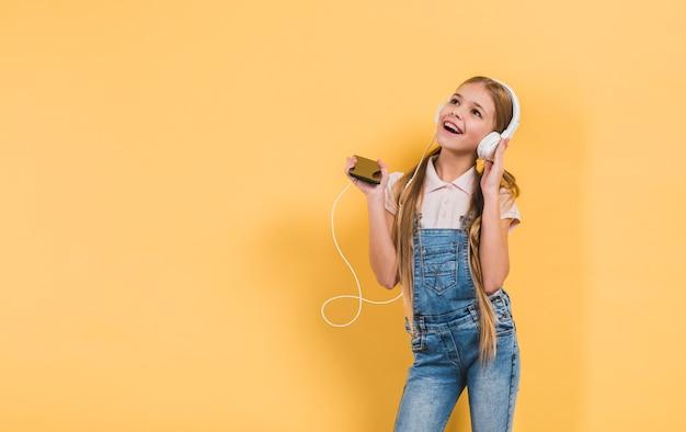 Muchacha feliz que disfruta de la música en el auricular que sostiene el teléfono móvil en la mano que se opone a fondo amarillo