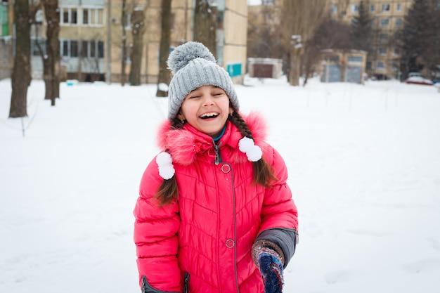 Muchacha feliz que juega en un patio en el día escarchado del invierno.