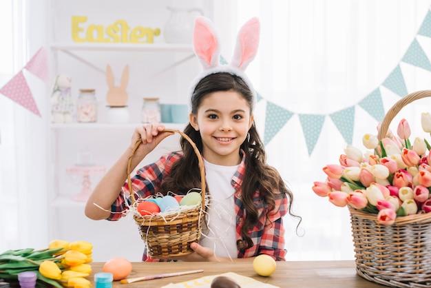 Muchacha feliz que lleva los oídos del conejito que sostienen la cesta de los huevos de pascua coloridos