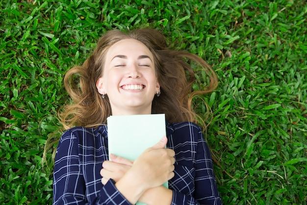 Muchacha feliz que miente en la hierba y que abraza el libro