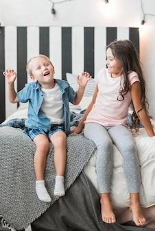 Muchacha feliz que mira al muchacho que se sienta en la cama que hace travesura