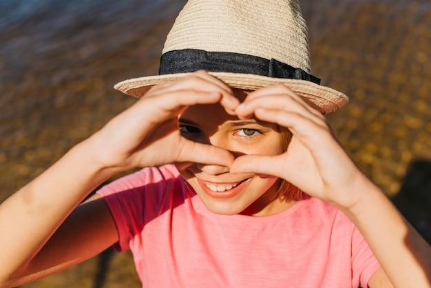 Muchacha feliz que muestra el corazón con las manos