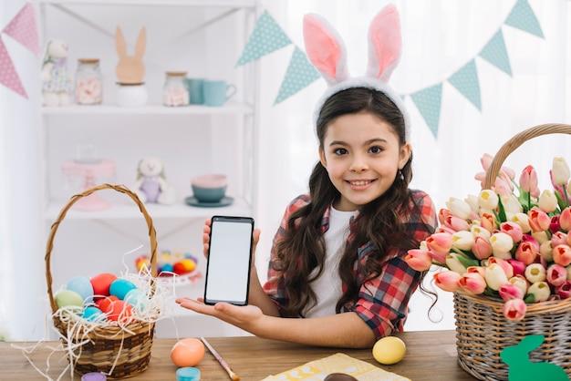 Muchacha feliz que muestra el teléfono móvil con los huevos de pascua y la cesta de los tulipanes en la tabla