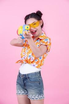 Muchacha feliz que sostiene un arma de agua rosado del fondo.