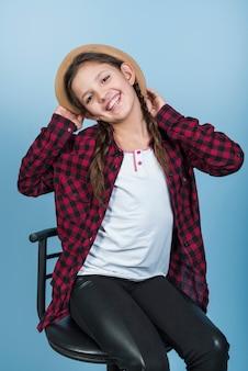 Muchacha feliz que sostiene el sombrero en la cabeza