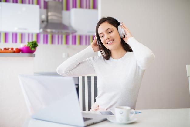 Muchacha feliz relajada joven con los auriculares en la mirada de la computadora portátil que bebe el café y que disfruta de música mientras que se sienta en la tabla de cocina.