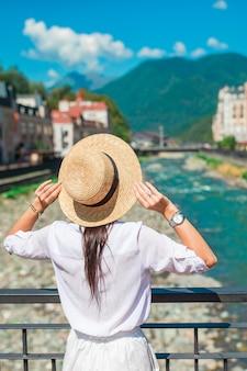 Muchacha feliz en el sombrero en el terraplén de un río de montaña en una ciudad europea.