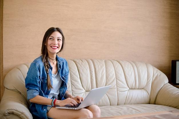 La muchacha feliz sonriente se comunica con alguien mientras sostiene una computadora portátil