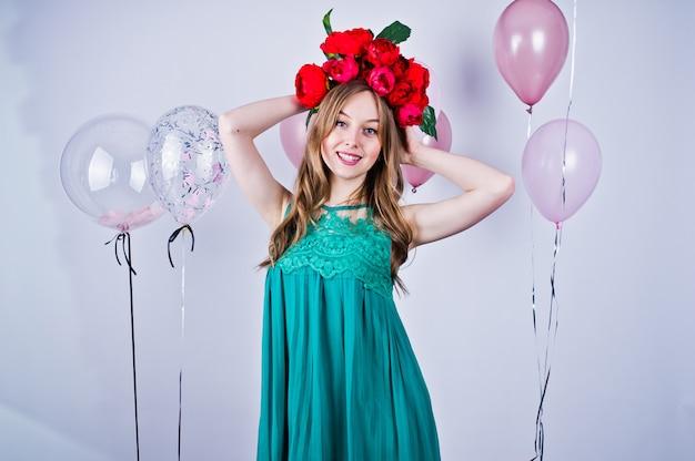 Muchacha feliz en vestido turquesa verde y guirnalda con globos de colores aislados en blanco. celebrando el tema de cumpleaños.