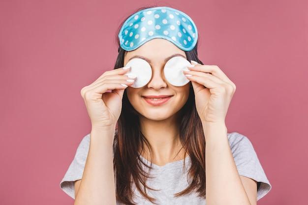 Muchacha fresca sana que quita maquillaje de su cara con algodón. mujer de la belleza que limpia su cara con la almohadilla de la esponja de algodón aislada en fondo rosado. concepto de belleza y cuidado de la piel. máscara para dormir.