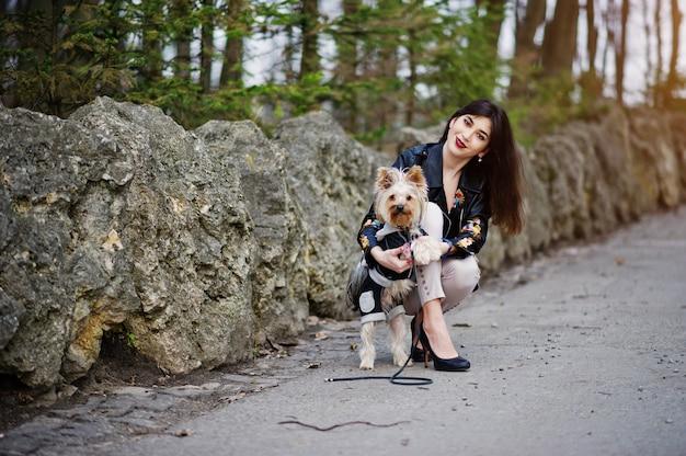 La muchacha gitana morena con el perro del yorkshire terrier presentó contra piedras en parque. modelo de chaqueta de cuero con adornos, pantalones y zapatos con tacones altos.