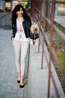 La muchacha gitana morena con el perro del yorkshire terrier presentó contra las verjas de acero. modelo de chaqueta de cuero con adornos, pantalones y zapatos con tacones altos.