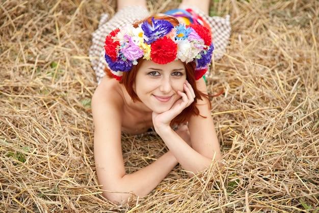 Muchacha en la guirnalda nacional eslava que miente en el campo.