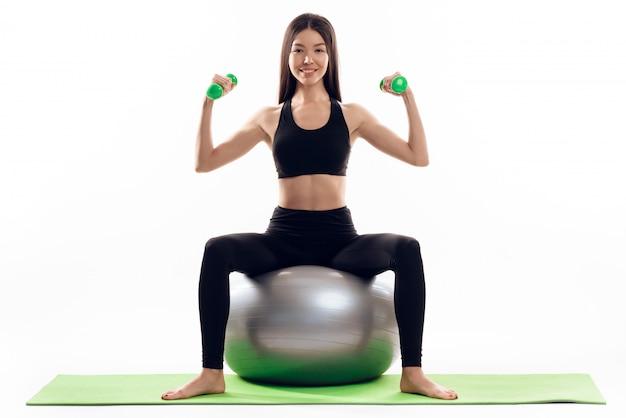 La muchacha hace ejercicios con pesas en la bola de la gimnasia.