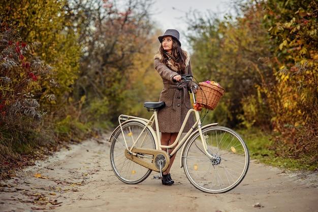 La muchacha hermosa en abrigo y el sombrero marrones del otoño que se colocan en el camino de tierra cerca de las señoras monta en bicicleta con la cesta llena de flores y de árboles del otoño en el fondo.
