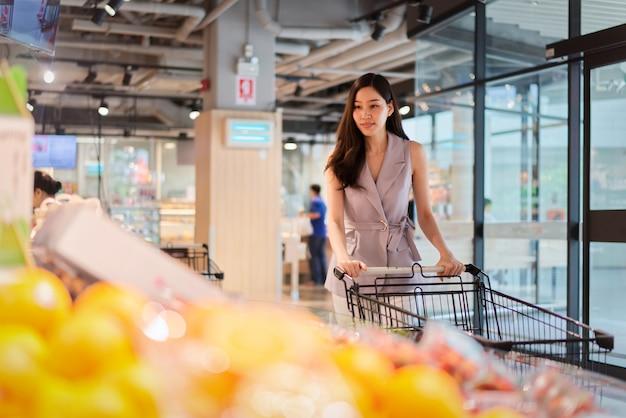 La muchacha hermosa asiática joven está eligiendo las frutas en supermercado.