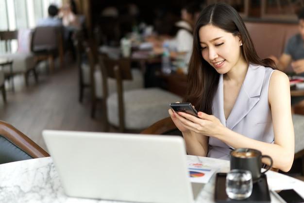 Muchacha hermosa asiática que se sienta en cafetería y que usa el teléfono móvil con sonrisa para entrar en contacto con al cliente.