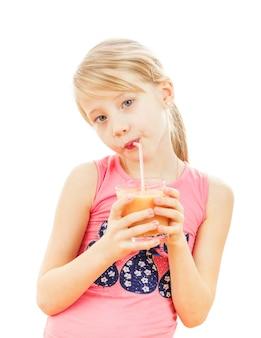 La muchacha hermosa bebe los smoothies del pomelo aislados en blanco.